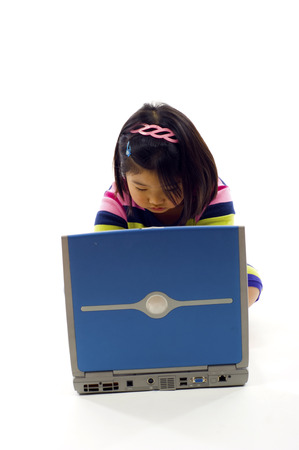 Closeup of little Asian girl working on laptop , isolated over white