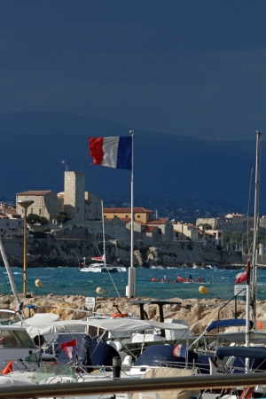 Antibes, France, August 31 2012, Torn French flag in windy conditions with the Picasso museum in the background