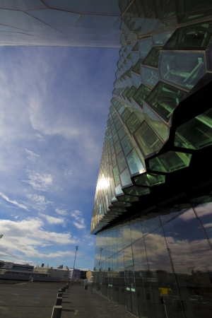 March 28th 2013. The fasade of the opera building in the harbour of Reykjavik, Iceland. The building glass fasades are bent through the wide angle lens with the sunkissed clouds in the sky as a background