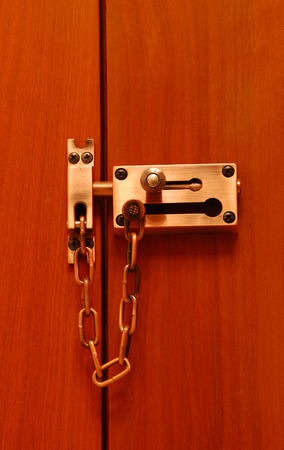 deadbolt: A double door lock with solid brass chain and surface bolt. Stock Photo
