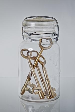 latchkey: Set of Vintage keys inside a glass jar.