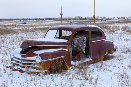 junk car: Old abandoned car covered with show in the countryside