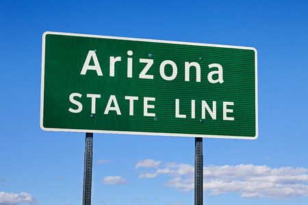 A Green Arizona State Line Road Sign Stock Photo