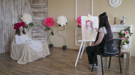 artist draws a portrait from nature. Beautiful model, with a wreath of scarlet peonies on his head, posing sitting in a white armchair Zdjęcie Seryjne