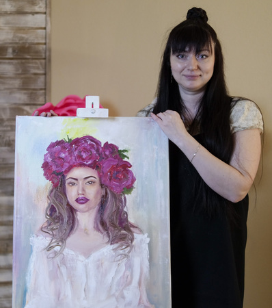 Beautiful model, with a wreath of scarlet peonies on the head. girl model painted on canvas. The artist shows her work, a portrait of a young model. Zdjęcie Seryjne