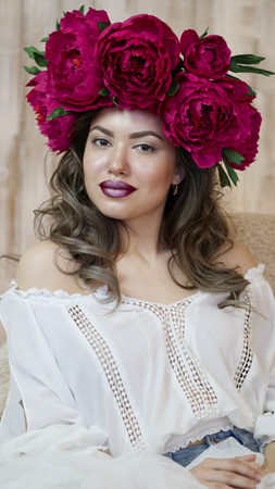 Girl model posing. a young woman in a wreath of scarlet peonies on her head, dark long curly hair descends on small shoulders