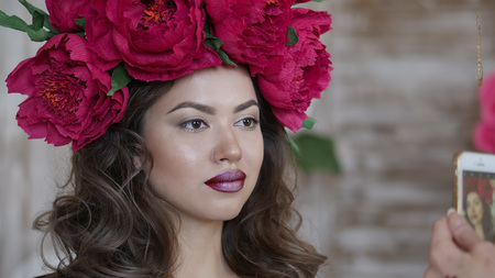 Beautiful model, with a wreath of scarlet peonies on his head. The model is photographed on the phone, a smartphone