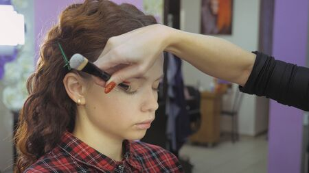 Easy Halloween Makeup. Girl in a beauty salon. Applying a stylistic pattern on the face of the model. The work of a master stylist.