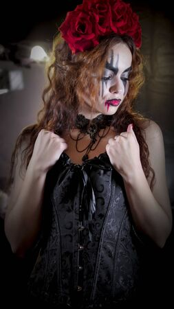 Easy Halloween Makeup. The girl with the picture on her face. The devils bride with a wreath of red flowers on her head. The woman is wearing a black corset dress and black stockings.