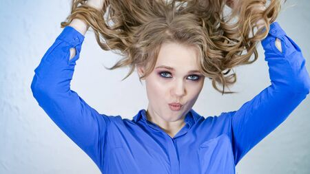 Young blonde girl lifts strands of hair up and throws them. Hair is flying in different directions. The face is hidden behind curls of hair. Clearly expressed emotions on the womans face.
