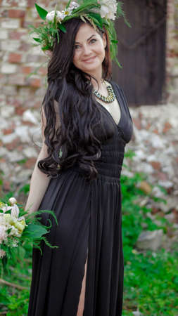 Woman in the spring. A wreath of meadow grass and flowers is worn on the brunettes head. White peonies adorn the head of a young lady. A girl in a long black sleeveless dress.