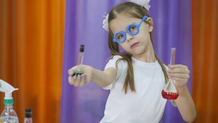 Child is holding flasks of colored liquid. Cute girl with blue round glasses on her face. Chemical experiments for children. Fun experiments for children. Children have fun and learn. Bright childrens emotions.
