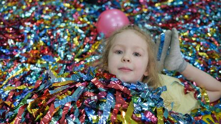 little girl is lying in colored strips of paper. Cute baby face. Archivio Fotografico