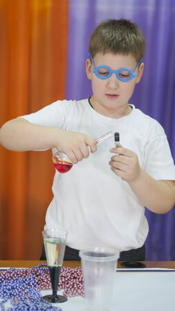 Boy with blue round glasses on his face. Child is holding flasks of colored liquid. Chemical experiments for children. Fun experiments for children. Children have fun and learn. Bright childrens emotions. 版權商用圖片