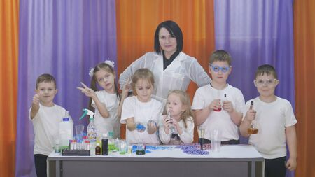 Child is holding flasks of colored liquid. Chemical experiments for children. Fun experiments for children. Children have fun and learn. Bright childrens emotions.