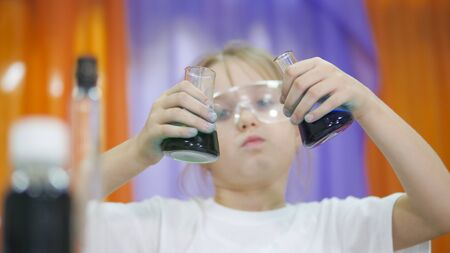Child is holding flasks of colored liquid. Cute girl in protective transparent glasses on her face. Chemical experiments for children. Fun experiments for children. Children have fun and learn. Bright childrens emotions.