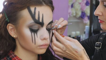 Easy Halloween Makeup. Eyelash extension black. Gluing the hair to the eyelashes. The hair prosthesis is brought to the person's face with tweezers. The face of a crying girl.