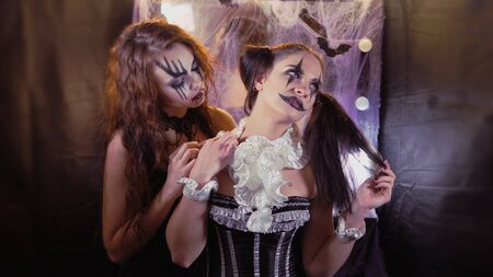 Maquillage of the actor. A woman wearing black corset dress. A girl with Halloween makeup is sitting in front of a mirror. The makeup of the actor. The girl in the image of the devil's Bride comes up and bites the neck of the clown girl. The woman pushes a tuft of hair away from her neck. Standard-Bild