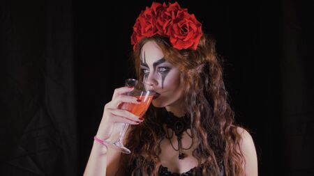 Easy Halloween Makeup. The girl with the picture on her face. The devils bride with a wreath of red flowers on her head. Woman drinks from a glass of red drink offering to drink to the viewer.