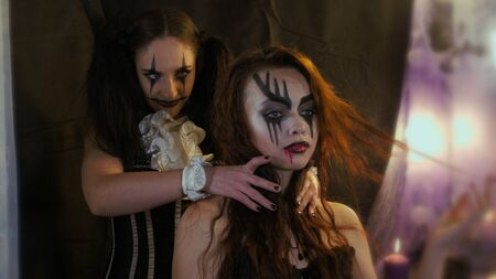 Easy Halloween Makeup. woman put her hands on the other girls neck. Horror in the eyes of a man. Peoples emotions. The girl with the picture on her face. Zdjęcie Seryjne