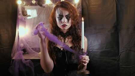 Easy Halloween Makeup. The girl with the picture on her face. Photo portrait. Woman holds a paraffin candle.