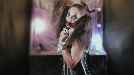 Portrait of a woman. A clown with a smile in corset with a white collar on the neck. Model with makeup for Halloween. Woman flirting. The girl with the red Lollipop. The woman takes a candy in her mouth and licks it. Zdjęcie Seryjne