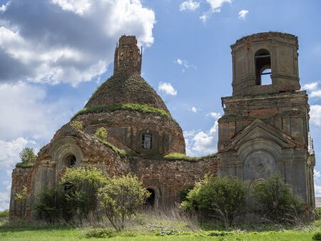 Ruins of an Orthodox Church against a blue sky with white clouds.