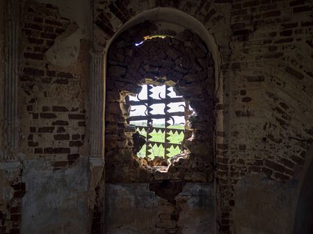 Windows of an ancient temple, in the wall of red brick, in the form of an arch. The hole in the wall is sealed with metal bars with teeth. Zdjęcie Seryjne