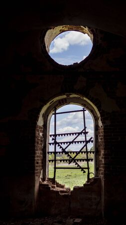 Windows of an ancient temple, in the wall of red brick, in the form of an arch. The hole in the wall is sealed with metal bars with teeth. Rose window in the wall of a ruined old Orthodox Church. Zdjęcie Seryjne