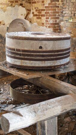 Old millstones, in ruins of red brick. Unused stone millstones in bird droppings.