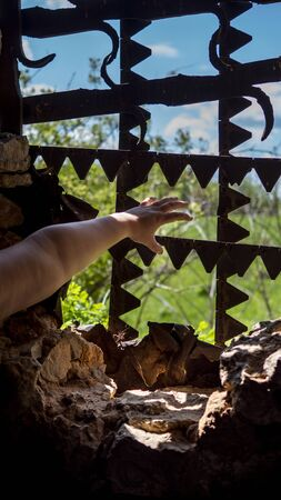 Hands reach for the metal bars in the window. Outside the window, the landscape was beautiful.