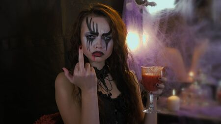 A woman with Halloween Makeup with a glass of wine