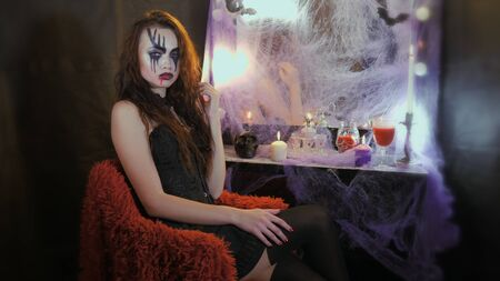 A woman with halloween makeup sitting in front of the mirror on a red chair. Фото со стока - 149908219