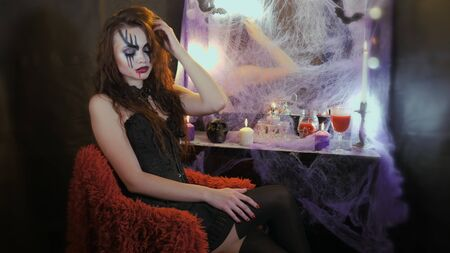 A woman with halloween makeup sitting in front of the mirror on a red chair.