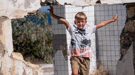 Blond boy on the ruins of the wall. Zdjęcie Seryjne