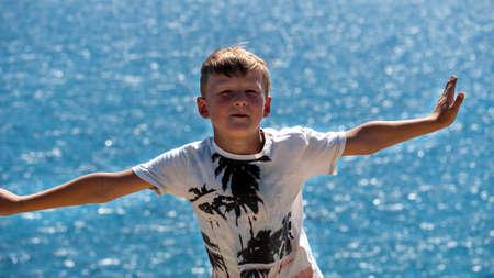 A fair-haired boy against the blue sea.