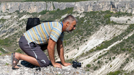 An adult man on the edge of the gorge, side view, is on all fours. Man over the gorge.