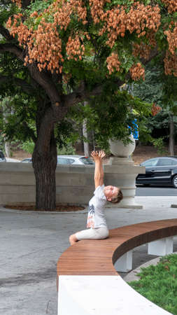 Boy pulls two hands up to the branches of the tree. Soap tree in an urban environment. The fruits of the original three-lobed shape are reddish-brown in color.