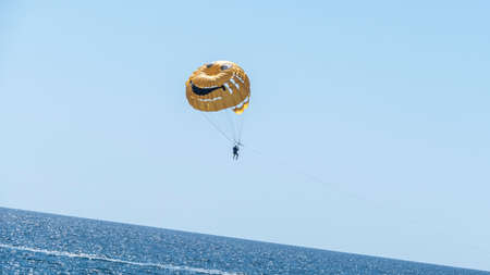 Water recreation. Launch a skydiver on a yellow parachute with a painted smile. Фото со стока - 156207085