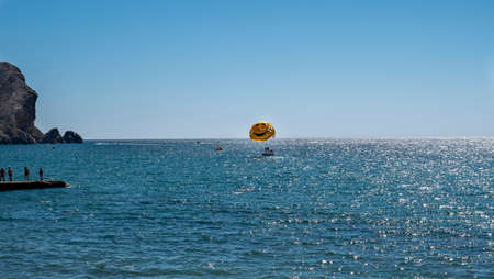 Water recreation. Launch a skydiver on a yellow parachute with a painted smile. Zdjęcie Seryjne