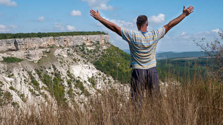 An adult man with his arms spread wide, seen from the back, stands on the edge of a precipice. Фото со стока - 156884114