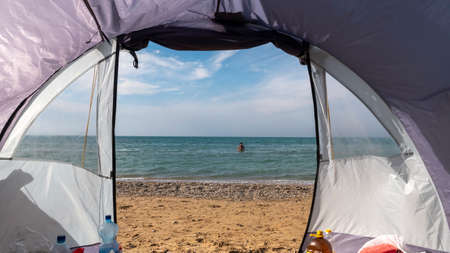 View through the open entrance to the tent on the sea. Sandy beach. Zdjęcie Seryjne