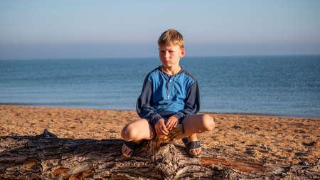 Portrait of a boy. A child is sitting on a log lying on the beach.