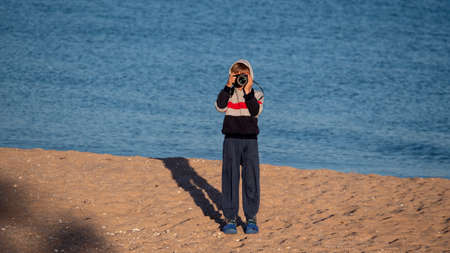 Child on the beach. The boy holds a camera in his hands. Zdjęcie Seryjne