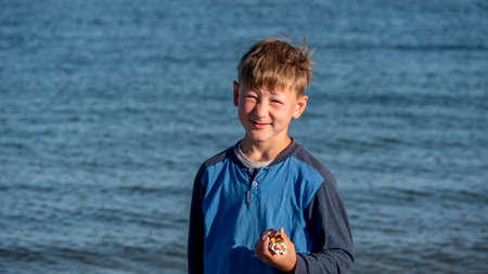 Portrait of a child against the sea. The boy holds the candy in his hands.