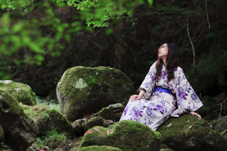 Woman wearing a kimono is a forest bathing. photo