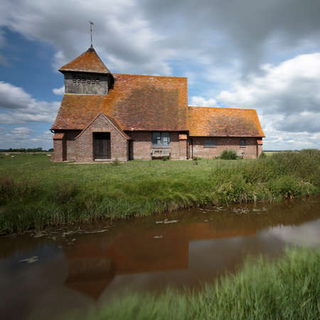 The church of St Thomas à Becket reflected in a canal near Brookland, Romney Marsh, England