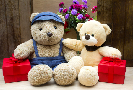 cute teddy bears in red gift box on wood background,too give someone important in valentine's day 免版税图像