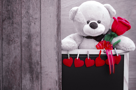 Cute teddy Bear toy clutching a red rose in its arms and blackboard decorate red heart on wood background for an anniversary or valentine's celebration with copy space,Valentine's day concept.