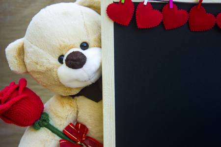 Valentine's day concept,Cute teddy Bear toy clutching a red rose in its arms and blackboard decorate red heart on wood background for an anniversary or valentine's celebration with copy space.